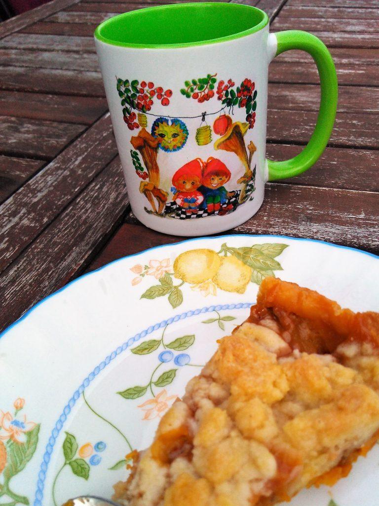 """Mein Mirabellen-Streuselkuchen. Im Hintergrund: Wichteltasse """"Laternenfest"""". Ein Original Julclub-Design."""